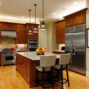 Design ideas for a traditional kitchen in DC Metro with a submerged sink, recessed-panel cabinets, medium wood cabinets, beige splashback, stainless steel appliances and medium hardwood flooring.