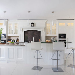 Example of a large transitional porcelain floor and white floor eat-in kitchen design in Other with an undermount sink, beaded inset cabinets, white cabinets, granite countertops, black backsplash, stone slab backsplash, black appliances and an island