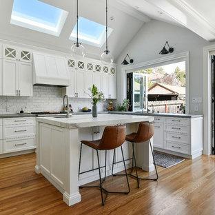 Удачное сочетание для дизайна помещения: п-образная кухня-гостиная среднего размера в стиле современная классика с врезной раковиной, фасадами в стиле шейкер, белыми фасадами, белым фартуком, техникой из нержавеющей стали, паркетным полом среднего тона, островом, коричневым полом, серой столешницей, столешницей из бетона и фартуком из мрамора - самое интересное для вас