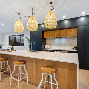 Inspiration för stora moderna vitt kök, med en undermonterad diskho, svarta skåp, kaklad bänkskiva, vitt stänkskydd, stänkskydd i stenkakel, rostfria vitvaror, mellanmörkt trägolv, en köksö, släta luckor och beiget golv