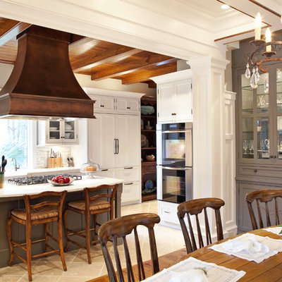 Eat-in kitchen - mid-sized traditional u-shaped limestone floor eat-in kitchen idea in Charleston with shaker cabinets, a farmhouse sink, white cabinets, marble countertops, beige backsplash, matchstick tile backsplash, stainless steel appliances and an island
