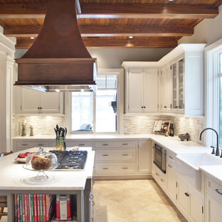 Неиссякаемый источник вдохновения для домашнего уюта: п-образная кухня среднего размера в классическом стиле с фасадами в стиле шейкер, раковиной в стиле кантри, обеденным столом, белыми фасадами, мраморной столешницей, бежевым фартуком, фартуком из удлиненной плитки, техникой из нержавеющей стали, полом из известняка и островом