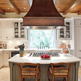 チャールストンの中サイズのトラディショナルスタイルのおしゃれなキッチン (シェーカースタイル扉のキャビネット、エプロンフロントシンク、白いキャビネット、大理石カウンター、ベージュキッチンパネル、ボーダータイルのキッチンパネル、シルバーの調理設備の、ライムストーンの床) の写真