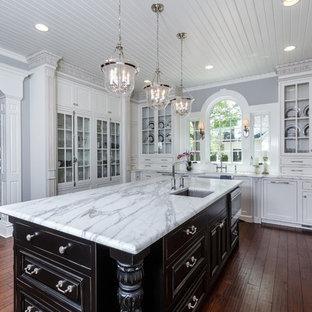 シンシナティの大きいヴィクトリアン調のおしゃれなキッチン (ガラス扉のキャビネット、白いキャビネット、大理石カウンター、アンダーカウンターシンク、白いキッチンパネル、サブウェイタイルのキッチンパネル、シルバーの調理設備の、無垢フローリング) の写真