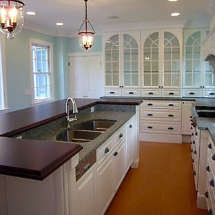 Large elegant galley medium tone wood floor eat-in kitchen photo in Providence with an island, raised-panel cabinets, white cabinets, granite countertops, white backsplash, stainless steel appliances and a double-bowl sink