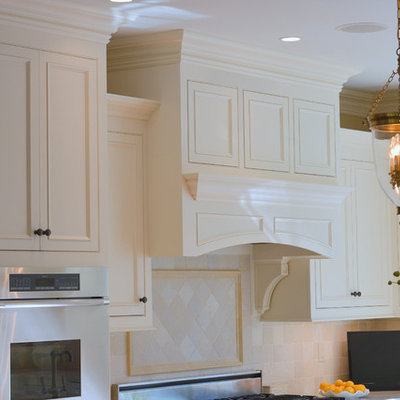 Large elegant u-shaped medium tone wood floor and brown floor eat-in kitchen photo in New York with an undermount sink, beaded inset cabinets, white cabinets, quartzite countertops, beige backsplash, stone tile backsplash, paneled appliances and an island
