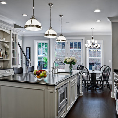 Example of a large classic galley dark wood floor eat-in kitchen design in Chicago with an undermount sink, recessed-panel cabinets, white cabinets, granite countertops, paneled appliances and an island