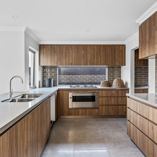 Photo of a contemporary u-shaped open plan kitchen in Perth with a double-bowl sink, flat-panel cabinets, medium wood cabinets, brown splashback, glass tile splashback, stainless steel appliances, a peninsula and beige floor.
