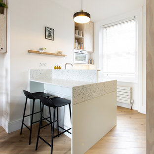 Small scandinavian open plan kitchen in London with a single-bowl sink, flat-panel cabinets, recycled glass benchtops, white splashback, stainless steel appliances, medium hardwood floors, with island and white benchtop.