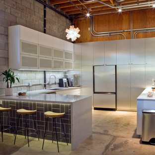 ロサンゼルスの中サイズのインダストリアルスタイルのおしゃれなキッチン (アンダーカウンターシンク、フラットパネル扉のキャビネット、白いキャビネット、クオーツストーンカウンター、マルチカラーのキッチンパネル、ガラスまたは窓のキッチンパネル、白い調理設備、コンクリートの床、グレーの床) の写真