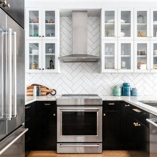 Modern inredning av ett litet gul gult kök, med en undermonterad diskho, luckor med glaspanel, svarta skåp, bänkskiva i kvarts, vitt stänkskydd, stänkskydd i porslinskakel, rostfria vitvaror, ljust trägolv, en halv köksö och brunt golv