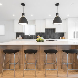Photo of a contemporary galley open plan kitchen in Vancouver with an undermount sink, shaker cabinets, white cabinets, quartzite benchtops, black splashback, ceramic splashback, panelled appliances, light hardwood floors, with island, yellow floor and multi-coloured benchtop.