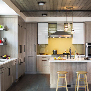 Contemporary kitchen designs - Trendy dark wood floor and brown floor kitchen photo in Denver with an undermount sink, flat-panel cabinets, medium tone wood cabinets, yellow backsplash, glass sheet backsplash, stainless steel appliances, an island and white countertops