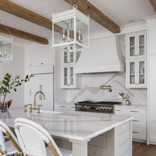 Farmhouse kitchen ideas - Example of a farmhouse galley medium tone wood floor and brown floor kitchen design in Other with a farmhouse sink, beaded inset cabinets, white cabinets, white backsplash, stainless steel appliances, an island and white countertops