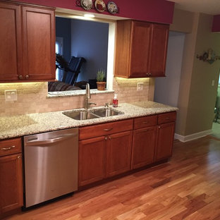 Example of a small transitional l-shaped medium tone wood floor eat-in kitchen design in Chicago with a double-bowl sink, recessed-panel cabinets, medium tone wood cabinets, laminate countertops, beige backsplash, subway tile backsplash and white appliances