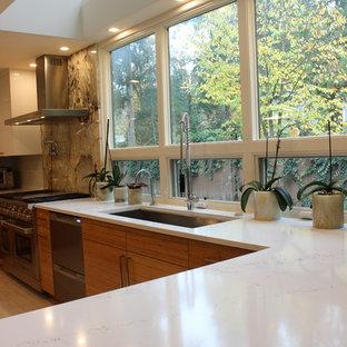 Große Moderne Küche in U-Form mit Vorratsschrank, Unterbauwaschbecken, flächenbündigen Schrankfronten, orangefarbenen Schränken, Granit-Arbeitsplatte, Küchenrückwand in Weiß, Küchengeräten aus Edelstahl, Porzellan-Bodenfliesen, Kücheninsel, weißem Boden und beiger Arbeitsplatte in Seattle