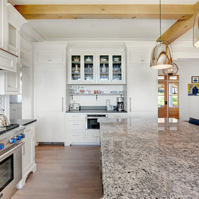 Example of a large farmhouse u-shaped brown floor and medium tone wood floor kitchen design in Baltimore with shaker cabinets, white cabinets, mosaic tile backsplash, paneled appliances, an island, a farmhouse sink and granite countertops