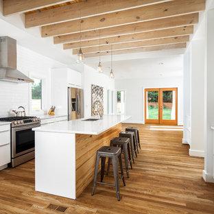 シャーロットの中サイズのカントリー風おしゃれなアイランドキッチン (フラットパネル扉のキャビネット、白いキャビネット、珪岩カウンター、白いキッチンパネル、サブウェイタイルのキッチンパネル、シルバーの調理設備の、無垢フローリング、白いキッチンカウンター、ダブルシンク) の写真