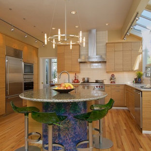 Photo of a contemporary l-shaped kitchen in Seattle with recycled glass benchtops, stainless steel appliances, flat-panel cabinets, medium wood cabinets, white splashback and subway tile splashback.