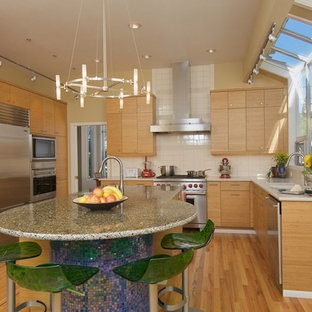 This is an example of a contemporary l-shaped kitchen in Seattle with stainless steel appliances, flat-panel cabinets, medium wood cabinets, recycled glass benchtops, white splashback and subway tile splashback.