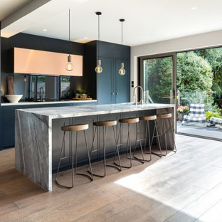Design ideas for a medium sized contemporary galley kitchen/diner in London with a built-in sink, flat-panel cabinets, blue cabinets, marble worktops, blue splashback, glass sheet splashback, black appliances, medium hardwood flooring, an island, brown floors and grey worktops.