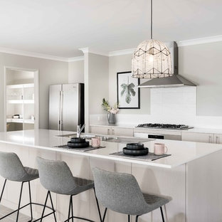 Photo of a mid-sized contemporary galley open plan kitchen in Perth with a double-bowl sink, flat-panel cabinets, beige cabinets, white splashback, stainless steel appliances, with island, grey floor, quartz benchtops, ceramic splashback and ceramic floors.