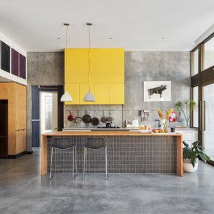 Foto de cocina de galera, urbana, de tamaño medio, con armarios con paneles lisos, suelo de cemento y una isla