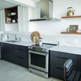バンクーバーの小さいモダンスタイルのおしゃれなキッチン (アンダーカウンターシンク、フラットパネル扉のキャビネット、黒いキャビネット、クオーツストーンカウンター、白いキッチンパネル、シルバーの調理設備の、セラミックタイルの床、ベージュの床、白いキッチンカウンター) の写真
