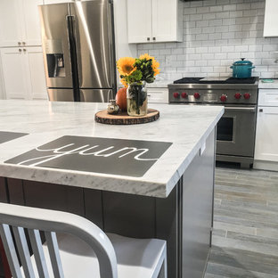 This is an example of a large country u-shaped kitchen/diner in Los Angeles with a belfast sink, recessed-panel cabinets, white cabinets, marble worktops, white splashback, metro tiled splashback, stainless steel appliances, porcelain flooring, an island, grey floors and white worktops.