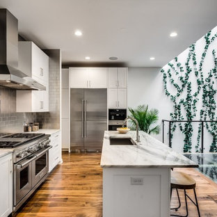 Transitional kitchen remodeling - Example of a transitional medium tone wood floor kitchen design in Chicago with an undermount sink, shaker cabinets, white cabinets, metallic backsplash, metal backsplash, stainless steel appliances and an island