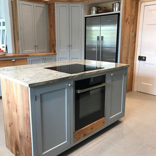 他の地域の中サイズのモダンスタイルのおしゃれなキッチン (中間色木目調キャビネット、木材カウンター、シルバーの調理設備、コンクリートの床、グレーの床、シェーカースタイル扉のキャビネット、グレーのキッチンパネル、グレーのキッチンカウンター) の写真