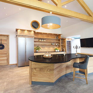 Design ideas for a large country kitchen in Other with an undermount sink, grey floor, black benchtop, open cabinets, medium wood cabinets, concrete floors, a peninsula, coloured appliances, granite benchtops and timber splashback.