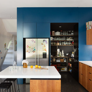 This is an example of a contemporary kitchen in Melbourne with flat-panel cabinets, medium wood cabinets, window splashback, stainless steel appliances, concrete floors, with island, grey floor and white benchtop.