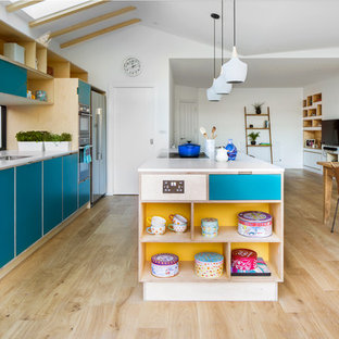 Modelo de cocina nórdica, abierta, con fregadero bajoencimera, armarios con paneles lisos, puertas de armario turquesas, salpicadero de vidrio, suelo de madera clara, una isla, suelo beige y encimeras blancas