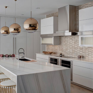This is an example of a large contemporary l-shaped kitchen/diner in Chicago with a submerged sink, flat-panel cabinets, white cabinets, metallic splashback, stainless steel appliances, an island, marble worktops, terracotta splashback and light hardwood flooring.