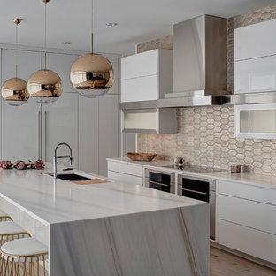 Idéer för ett stort modernt kök, med en undermonterad diskho, släta luckor, vita skåp, stänkskydd med metallisk yta, rostfria vitvaror, en köksö, marmorbänkskiva, stänkskydd i terrakottakakel och ljust trägolv