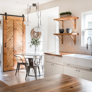 Small farmhouse kitchen photos - Example of a small country u-shaped laminate floor and gray floor kitchen design in Sacramento with a farmhouse sink, shaker cabinets, white cabinets, wood countertops, stainless steel appliances, white backsplash, subway tile backsplash and brown countertops