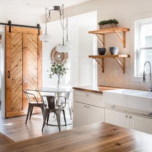 サクラメントの小さいカントリー風おしゃれなコの字型キッチン (エプロンフロントシンク、シェーカースタイル扉のキャビネット、白いキャビネット、木材カウンター、シルバーの調理設備の、ラミネートの床、グレーの床、白いキッチンパネル、サブウェイタイルのキッチンパネル、茶色いキッチンカウンター) の写真