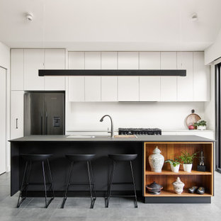 Design ideas for a contemporary galley eat-in kitchen in Melbourne with a drop-in sink, flat-panel cabinets, white cabinets, stainless steel appliances, with island, grey floor, grey benchtop, quartz benchtops, white splashback and cement tiles.