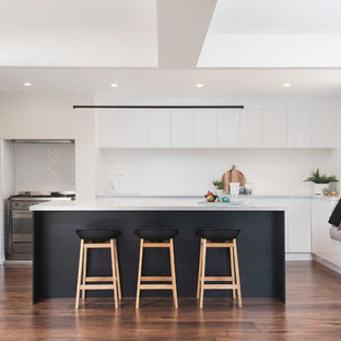 This is an example of a large contemporary kitchen in Other with an undermount sink, white cabinets, quartz benchtops, white splashback, ceramic splashback, stainless steel appliances, medium hardwood floors, with island, brown floor, white benchtop and flat-panel cabinets.