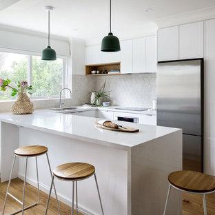メルボルンの小さいコンテンポラリースタイルのおしゃれなキッチン (ダブルシンク、白いキャビネット、クオーツストーンカウンター、ベージュキッチンパネル、セラミックタイルのキッチンパネル、シルバーの調理設備の、茶色い床、白いキッチンカウンター、フラットパネル扉のキャビネット、無垢フローリング) の写真