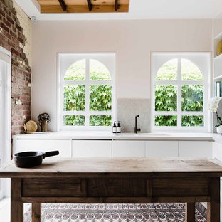 Inspiration for a mediterranean l-shaped separate kitchen in Melbourne with an integrated sink, flat-panel cabinets, white cabinets, beige splashback, mosaic tile splashback, panelled appliances, with island, beige floor and beige benchtop.