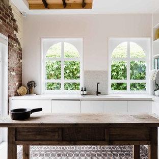 メルボルンの地中海スタイルのおしゃれなキッチン (一体型シンク、フラットパネル扉のキャビネット、白いキャビネット、ベージュキッチンパネル、モザイクタイルのキッチンパネル、パネルと同色の調理設備、ベージュの床、ベージュのキッチンカウンター) の写真
