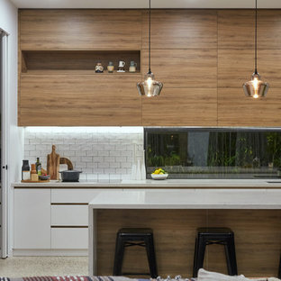 Photo of a contemporary l-shaped kitchen in Melbourne with an undermount sink, flat-panel cabinets, medium wood cabinets, white splashback, window splashback, panelled appliances, concrete floors, with island, grey floor and grey benchtop.