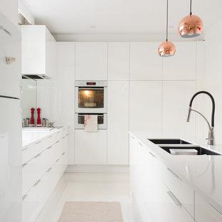 メルボルンのコンテンポラリースタイルのおしゃれなキッチン (アンダーカウンターシンク、フラットパネル扉のキャビネット、白いキャビネット、御影石カウンター、ミラータイルのキッチンパネル、白い調理設備、磁器タイルの床) の写真