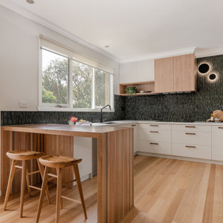 Inspiration for a contemporary u-shaped kitchen in Melbourne with an undermount sink, flat-panel cabinets, white cabinets, black splashback, panelled appliances, light hardwood floors, a peninsula, beige floor and white benchtop.