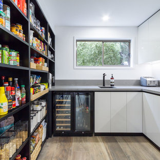 Expansive contemporary u-shaped eat-in kitchen in Melbourne with flat-panel cabinets, quartz benchtops, white splashback, stainless steel appliances, porcelain floors, with island, brown floor, an undermount sink, white cabinets and grey benchtop.