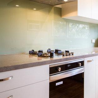 メルボルンの小さいコンテンポラリースタイルのおしゃれなキッチン (ドロップインシンク、フラットパネル扉のキャビネット、白いキャビネット、ラミネートカウンター、緑のキッチンパネル、ガラス板のキッチンパネル、無垢フローリング、アイランドなし) の写真