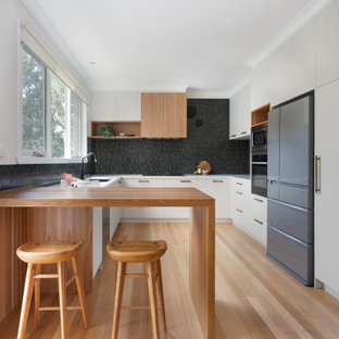 Photo of a contemporary u-shaped kitchen in Melbourne with an undermount sink, flat-panel cabinets, grey cabinets, black splashback, mosaic tile splashback, stainless steel appliances, light hardwood floors, a peninsula, beige floor and white benchtop.
