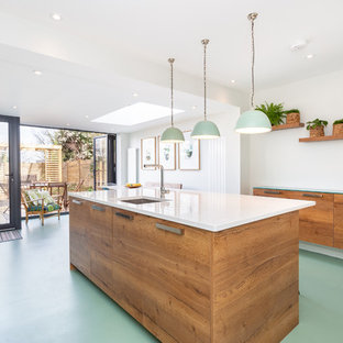This is an example of a contemporary galley kitchen in London with a submerged sink, flat-panel cabinets, medium wood cabinets, an island, green floors and white worktops.
